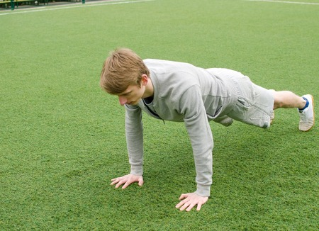 Young man making push ups on the green field Stock Photo