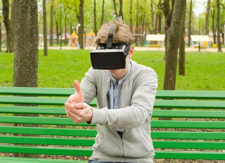 Young man using virtual glasses in the park Stock Photo