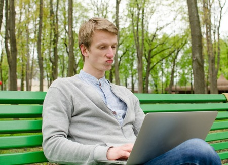 Young man using his laptop in the park Stock Photo