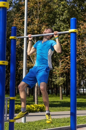 sportsman: Young sportsman making exersises in the park