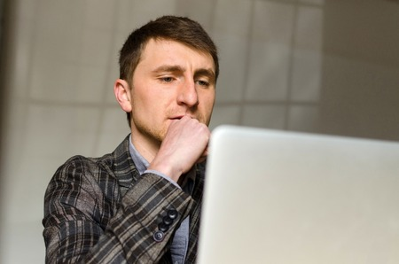 Close-up photo of young man with laptop thinking