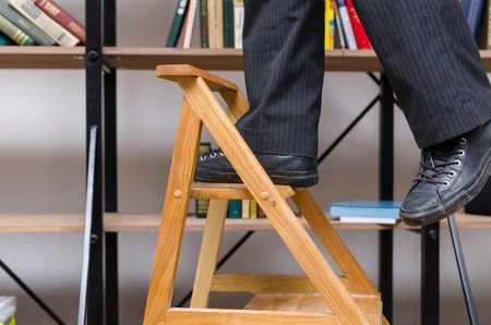 shelfs: Man climbing the brown stairs in the library