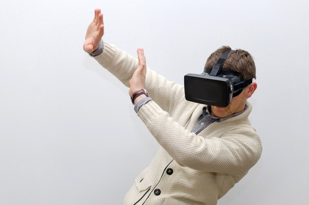 Man in virtual glasses imagining that smth is falling on him