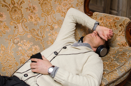 comfort room: Young man is listening music on sofa and sleeping