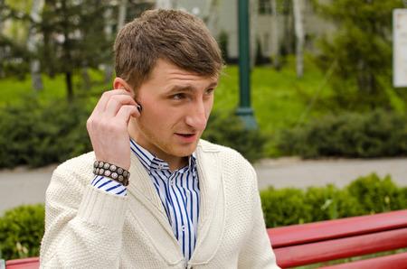 handsfree phones: Man talking in park Stock Photo