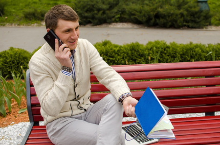 Young man is talking on the phone and sitting on a bench