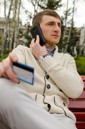 Young man is talking on the phone with blue card in right hand Stock Photo