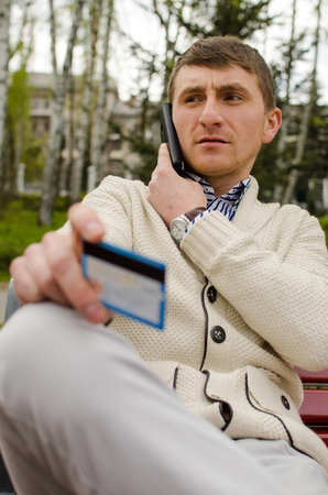 Young serious man is talking on the phone with card in his hand