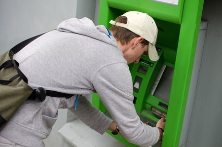 pin code: Young man is using cash machine on the street Stock Photo