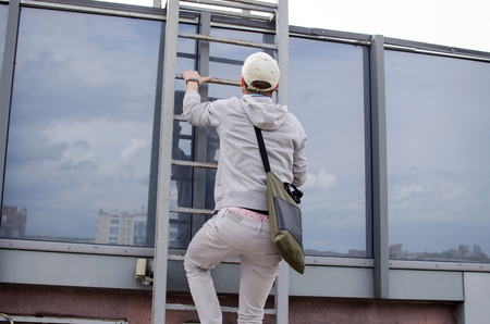 rood: Young man climbing up to the roof of the building Stock Photo