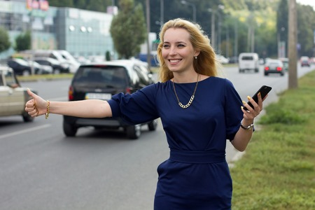 catching taxi: Young woman with cellphone  is catching the taxi on the street Stock Photo