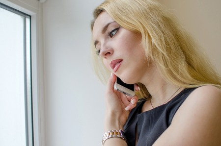 Young woman talking in the office on the phone