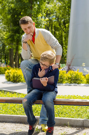 Young man is helping teenager to read a book in the park