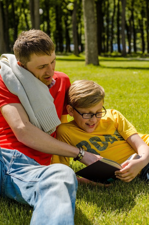 Young man is reading a book with teenager in the park Stock Photo