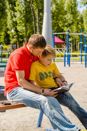 Teenager is reading a book with young man in the park Stock Photo