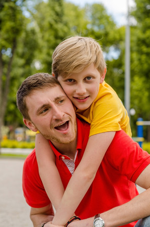 Young man is playing with teenager in the park Stock Photo