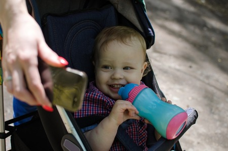 colored bottle: Young mother is walking with her small child in the park Stock Photo