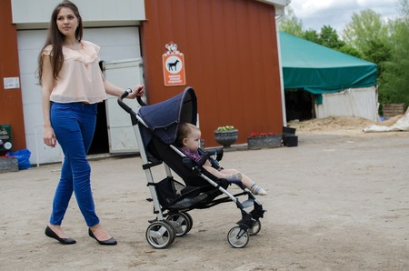 human relations: Young mother is walking with her small child in the park Stock Photo
