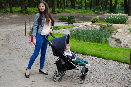 Young mother is walking with her small child in the park Stock Photo