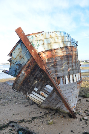 Ship wreck rotting on the beach in Brittany France. Rusted iron and decomposing wood