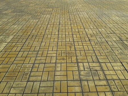 Das Muster der Fliesen auf der gelben Kopfsteinpflasterstraße des Bodens