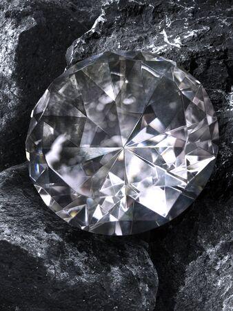 Photo of a single cut diamond on a piece of coal against a plain background