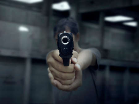 Man pointing a gun at the target on dark background