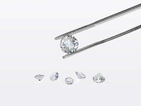 brilliant cut diamond held by tweezers isolated on white background