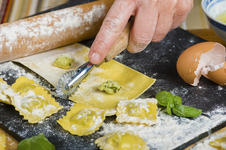 Preparing ravioli in the kitchen with tools and ingredients : dough, flour, eggs, stuffing, cutter, roller, board.