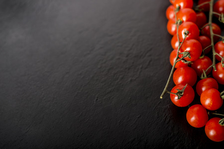healthful: Cherry tomatoes over a black stone plate with copy space.
