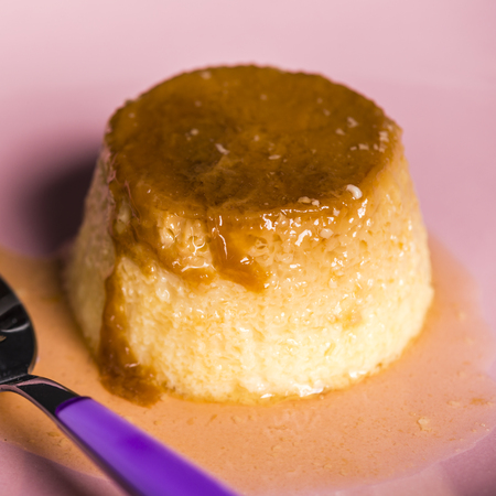 Flan - a sweet custard creme caramel with creme on top, on a pink plate over a wooden board. Stock Photo