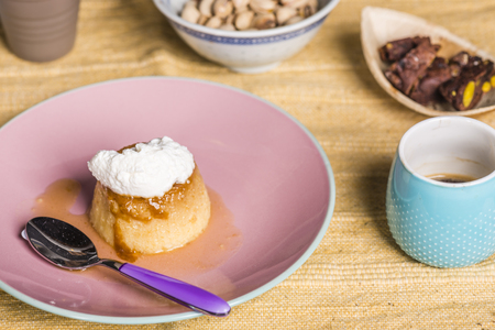 snacking: Flan -  creme on top, on a pink plate over a wooden board, served with chocolate cookies, dulce de leche confection , coffee and nuts.