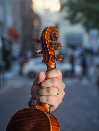 Male adult violinist hand holding antiquized handmade cremonese violin in the street at dawn in city street waiting to re start and play again in concert after coronavirus outbreaak