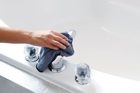 higienizar: Womans hand with microfiber cloth cleaning chrome tap