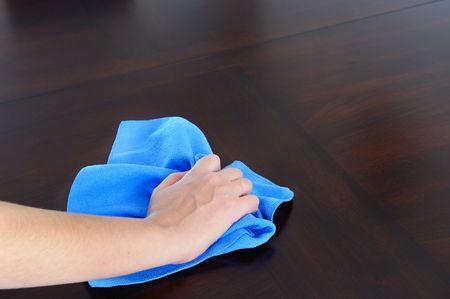 womans hand with microfiber cloth polishing dark wood photo