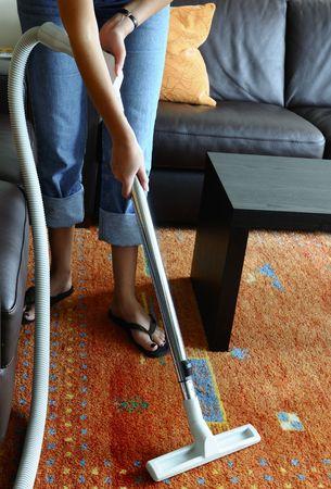 central: Mujer limpiando una alfombra con la aspiradora central  Foto de archivo