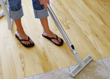 vacuuming: woman cleaning hardwood and tile floor with central vacuum cleaner