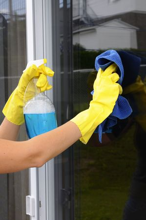 cleaning window: woman polishing glass door using microfiber cloth and yellow latex gloves Stock Photo