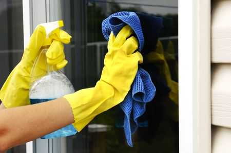 latex: woman polishing glass door using microfiber cloth and yellow latex gloves Stock Photo