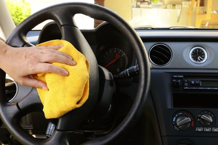 Womans nand with microfiber cloth polishing steering wheel of an SUV car photo