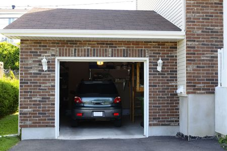 car in garage: SUV car in a garage next to the entrance to a house