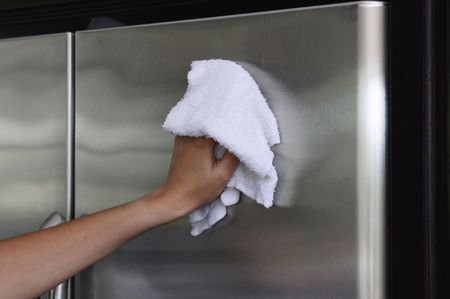 disinfect: Womans hand with cotton rag polishing a stainless stell fridge door