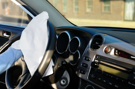 Womans hand with white rag cleaning cars steering wheel and front panel