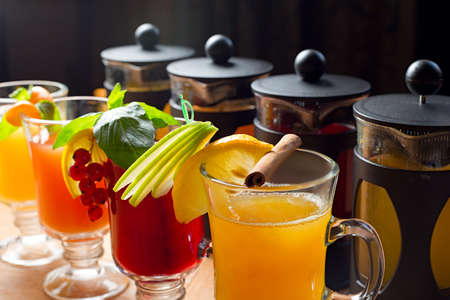 tastes: four teapots and glasses with different colors fruit tastes of tea
