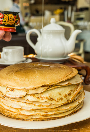 A stack of thin pancakes with honey and butter Stock Photo
