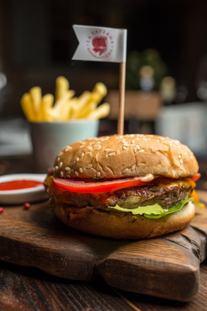 catsup: burger with beef and french fries on wooden board,  restaurant