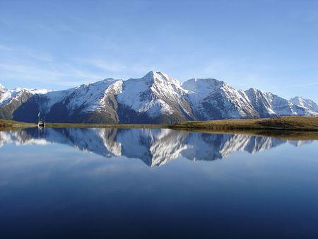 Reflexión en el agua de la tranquila y hermosa Bettmersee Lago, región de Aletsch, Valais, Suiza. Foto de archivo