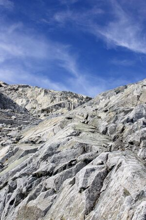 Mountain Rocks And Beautiful White Fluffy Clouds In the Blue Sky Stock Photo
