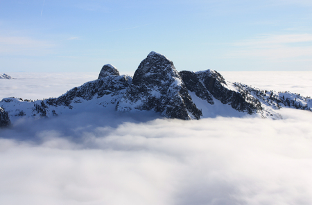 The Lions above the clouds in North Shore Mountains, BC, Canada. These two mountains can be seen from many locations around Vancouver and they stand as landmarks that define the skyline that this Canadian city is famous for.