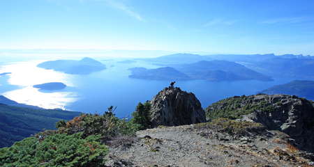 Hiker on the ridge of Mount Brunswick in Cypress Provincial Park near Vancouver, British Columbia, Canada. The spectacular Howe Sound, North Americas southernmost fjord in the background.